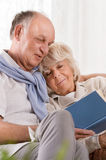 Senior man reading book. Senior men reading book and embracing sleeping wife Stock Photo