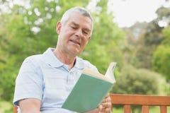 Senior man reading a book at park Royalty Free Stock Images