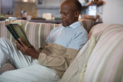 Senior man reading book while relaxing on sofa. In living room at home Stock Photos