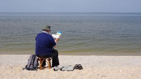 Senior man reading book sitting on a beach stock video footage