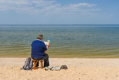Senior man reading book sitting on a beach Stock Photos