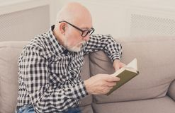 Senior man reading book at home, copy space Stock Images