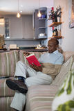 Senior man reading book while sitting on sofa. In living room at home Stock Photo