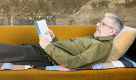 Senior man reading a book in sofa bed outdoors Royalty Free Stock Photography