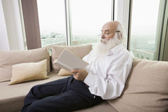 Senior man reading book on sofa in house Royalty Free Stock Photos