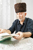 Senior man reading book at table Stock Photo