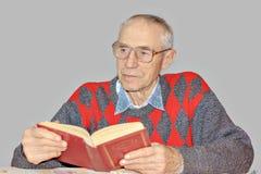 Senior man reading a book at the table. Senior man is reading book at the table in the bedroom Grey background Royalty Free Stock Photo