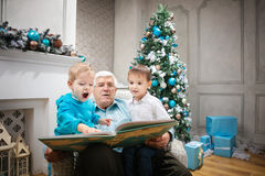 Senior man reading a book to grandsons Stock Image
