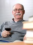 Senior man reading books with a glass of wine Stock Photo
