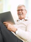 Senior man reading an e-book Stock Photography