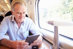 Senior Man Reading E Book On Train Journey Royalty Free Stock Photos