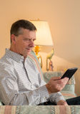 Senior man reading eBook on couch Royalty Free Stock Image