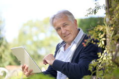 Senior man reading email on tablet. Senior man websurfing on tablet in home garden Royalty Free Stock Photography