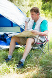 senior man reading beside his tent Royalty Free Stock Images