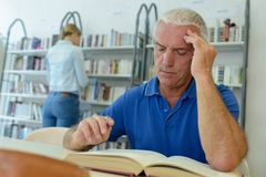Senior man reading indoors stock image