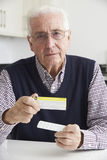 Senior Man Reading Information On Drug Packaging. Portrait Of Senior Man Reading Information On Drug Packaging Royalty Free Stock Image
