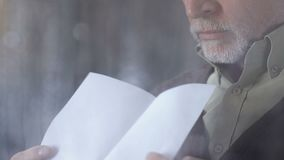 Senior man reading letter near rainy window and sighing, break-up, divorce