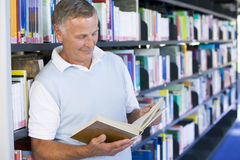 Senior man reading in a library.  Royalty Free Stock Photography