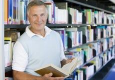 Senior man reading in a library.  Stock Photos