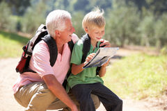 Senior man reading map with grandson on country wa royalty free stock image