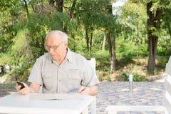 Senior man reading a message on his mobile Royalty Free Stock Photos