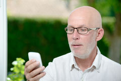Senior man reading message on smartphone Royalty Free Stock Photography
