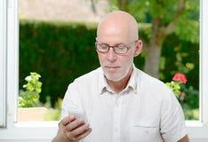 Senior man reading message on smartphone Stock Photo