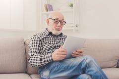 Senior man reading news on digital tablet Royalty Free Stock Photography