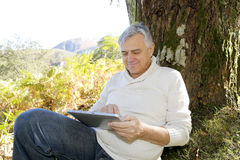 Senior man reading news on tablet outdoors Royalty Free Stock Images