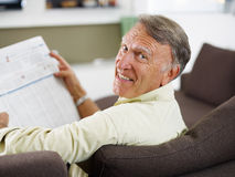 Senior man reading newspaper. At home and looking over shoulders Royalty Free Stock Photo