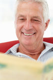 Senior man reading newspaper. Senior man sitting on sofa reading newspaper Royalty Free Stock Image