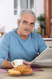 Senior man reading newspaper at breakfast Stock Photo