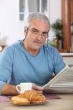 Senior man reading newspaper at breakfast Stock Photo