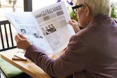 Senior Man Reading Newspaper at Breakfast Royalty Free Stock Images