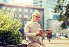 Senior man reading newspaper and drinking coffee royalty free stock photos