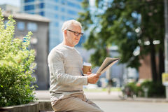 Senior man reading newspaper and drinking coffee Royalty Free Stock Photo