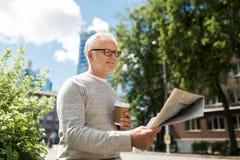 Senior man reading newspaper and drinking coffee Stock Photos