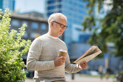 Senior man reading newspaper and drinking coffee Stock Images