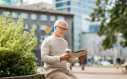 Senior man reading newspaper and drinking coffee Royalty Free Stock Photography