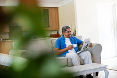 Senior man reading newspaper while having coffee Stock Images