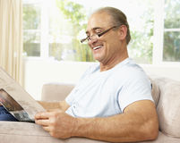 Senior Man Reading Newspaper At Home Stock Images