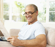 Senior Man Reading Newspaper At Home Royalty Free Stock Photo