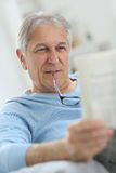 Senior man reading newspaper. Senior man at home reading newspaper Stock Photography