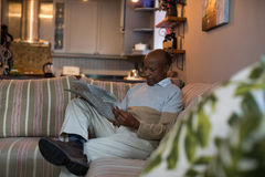 Senior man reading newspaper at home. Senior man reading newspaper while sitting on sofa at home Royalty Free Stock Photos