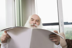 Senior man reading newspaper in house Stock Photography