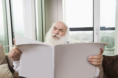 Senior man reading newspaper in house Royalty Free Stock Images