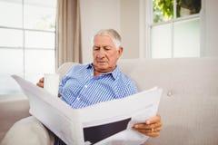 Senior man reading newspaper in living room Stock Image