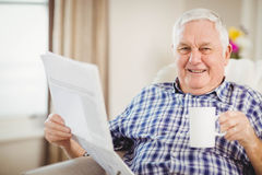 Senior man reading newspaper in living room Royalty Free Stock Photography