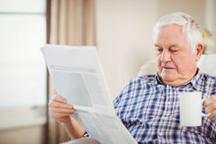 Senior man reading newspaper in living room Royalty Free Stock Photo