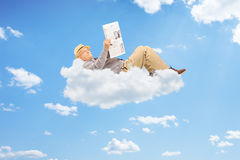 Senior man reading newspaper and lying on clouds Royalty Free Stock Photo